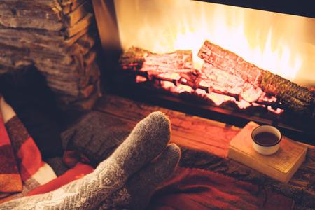 冷たい秋や冬の夜。毛布、お茶、火で休んでいる人々。ウールの靴下の足のクローズ アップ写真。居心地の良いシーン。 写真素材
