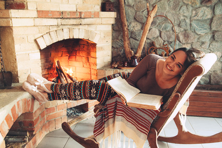 Woman reading book and relaxing by the fire place some cold evening, winter weekends, cozy scene Stock Photo