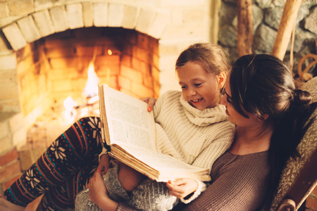 chilling: Mom with child reading book and relaxing by the fire place some cold evening, winter weekends, cozy scene