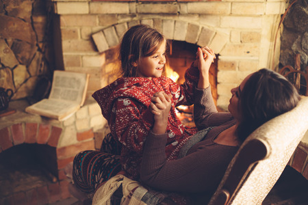 warmth: Mom with child playing and chilling by the fire place some cold evening, winter weekends, cozy scene