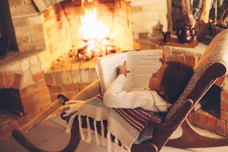 Frauenlesebuch und Entspannen am Kamin einige kalten Abend, Winterwochen, gemütliche Szene