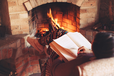 Woman reading book and relaxing by the fire place some cold evening, winter weekends, cozy scene Foto de archivo