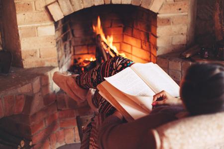 Vrouw leesboek en ontspannen bij de open haard een aantal koude avond, winter weekends, gezellige scene