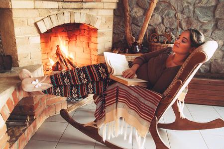 화재 장소에 의해 책을 읽고 여자 편안한 약간 추운 저녁, 겨울 주말, 아늑한 장면 스톡 콘텐츠
