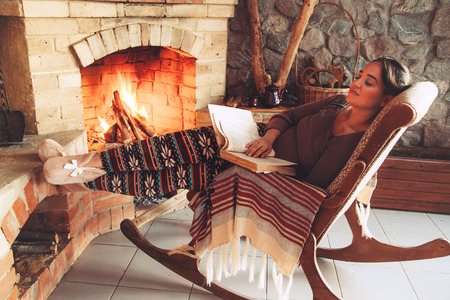 Woman reading book and relaxing by the fire place some cold evening, winter weekends, cozy scene Фото со стока