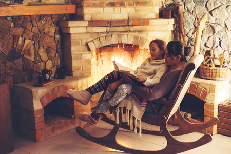 Mom with child reading book and relaxing by the fire place some cold evening, winter weekends, cozy scene 版權商用圖片 - 63235571