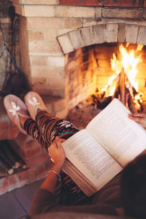 女の本を読んで、火によってリラックス場所いくつかの寒い夜、冬の週末、居心地の良いシーン