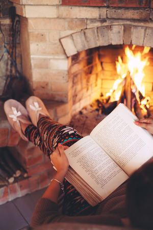 Woman reading book and relaxing by the fire place some cold evening, winter weekends, cozy scene 版權商用圖片 - 63235572