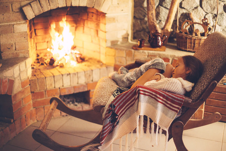 log book: Woman reading book and relaxing by the fire place some cold evening, winter weekends, cozy scene Stock Photo
