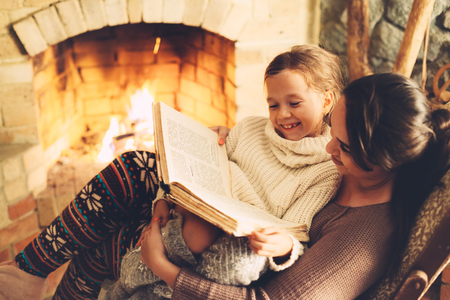 Mom with child reading book and relaxing by the fire place some cold evening, winter weekends, cozy scene Imagens - 63235597