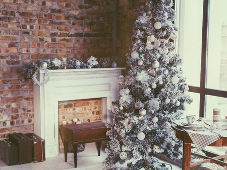 furniture home: Winter home decor. Christmas tree in loft interior against brick wall. Old vintage furniture. Stock Photo