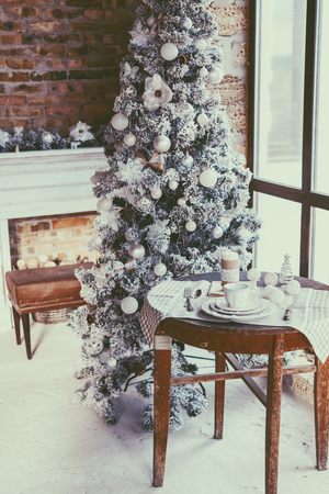 old furniture: Winter home decor. Christmas tree in loft interior against brick wall. Old vintage furniture. Stock Photo