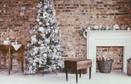 la decoración del hogar de invierno. el árbol de navidad en el interior de loft contra la pared de ladrillo. muebles de época antigua.