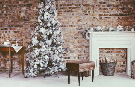 vintage furniture: Winter home decor. Christmas tree in loft interior against brick wall. Old vintage furniture. Stock Photo