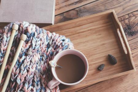 trompo de madera: Tejido de punto, agujas, libro y café en una bandeja de madera, vista desde arriba. fin de semana de invierno, escena acogedora.