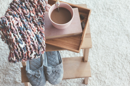 Knitting, needles, book and coffe on a wooden tray, top view. Winter weekend, cozy scene.