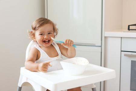 Schattige baby 1,4 jaar oud zitten op een hoge kinderstoel en het eten van groente alleen in witte keuken Stockfoto