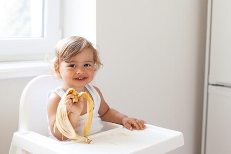banane: Bébé mignon 1,4 ans assis sur une chaise haute pour les enfants et de manger des fruits seuls dans la cuisine blanche
