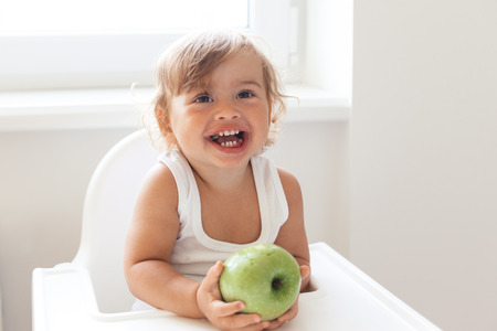 4 years old: Cute baby 1,4 years old sitting on high children chair and eating fruit alone in white kitchen