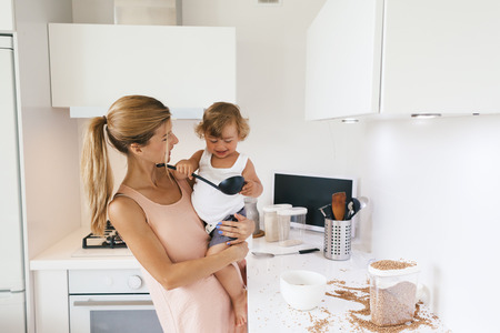 4 years old: Mom with her 1,4 years old child cooking in the white kitchen interior Stock Photo