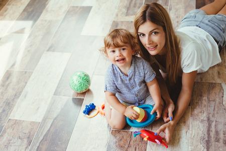 ママの暖かいきれいな床を自宅におもちゃで息子と遊ぶ