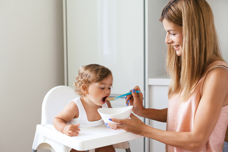 highchair: Mom feeding baby with spoon of 1,4 years old in white kitchen