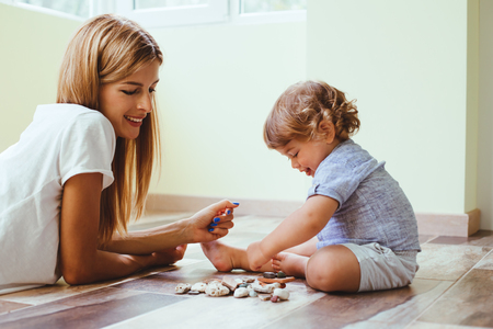 Mom playing with her son with toys on the warm clean floor at home photo