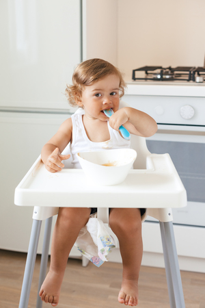 Cute baby 1,4 years old sitting on high children chair and eating vegetable alone in white kitchen photo
