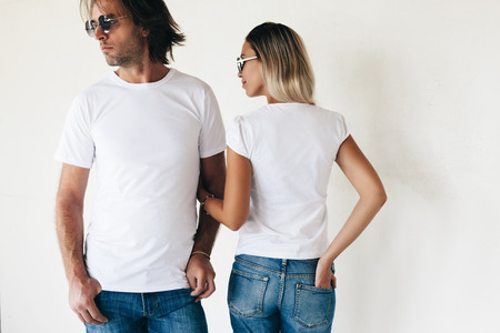 Two hipster models man and woman wearing blanc t-shirt, jeans and sunglasses posing against white wall, toned photo, front and back tshirt mockup for couple Stock Photo