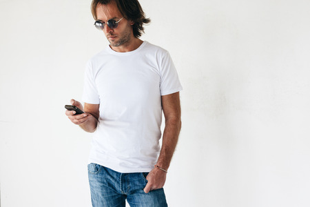 Man draagt blanc t-shirt poseren tegen witte muur, afgezwakt foto, front tshirt mockup op model