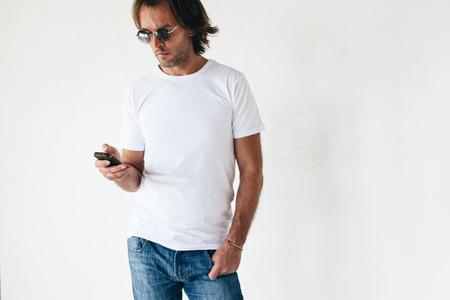 Uomo che indossa blanc t-shirt in posa contro il muro bianco, tonica foto, tshirt mockup anteriore del modello