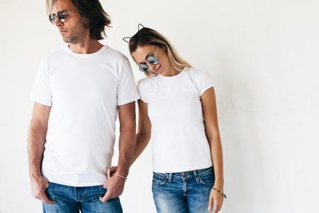 Два битнику модели мужчины и женщины носили блан футболку, джинсы и солнцезащитные очки, создавая против белой стене, тонированное фото, передний тенниску макет для пары