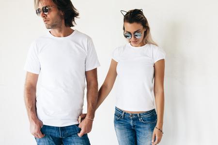 2 つの流行に敏感なモデル男と女・ ブランを身に着けている t シャツ、ジーンズと白い壁、ポージング サングラス トーンの写真のカップルのための