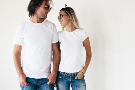 Dois modelos de hipster homem e mulher vestindo blanc t-shirt, jeans e óculos de sol posando contra a parede branca, foto tonificada, mockup frente maquete para casal