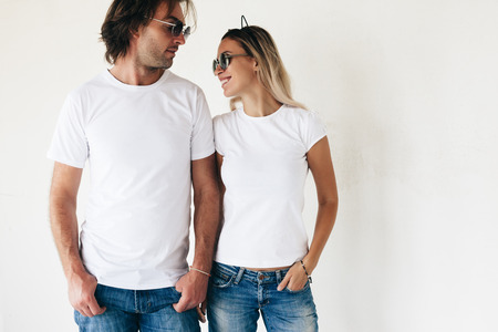 兩個時髦機型的男人和女人穿相思T卹,牛仔褲和太陽鏡冒充對白色的牆,照片色調,前T卹樣機情侶