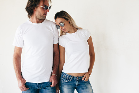 tshirts: Two hipster models man and woman wearing blanc t-shirt, jeans and sunglasses posing against white wall, toned photo, front tshirt mockup for couple