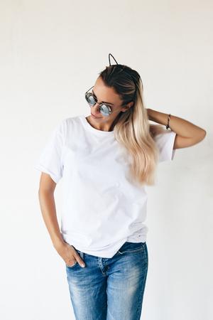 Donna che porta blanc maglietta in posa contro il muro bianco, tonica foto, maglietta mockup anteriore del modello, stile di vita bassa