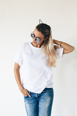 Woman wearing blanc t-shirt posing against white wall, toned photo, front tshirt mockup on model, hipster style