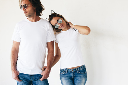 Two hipster models man and woman wearing blanc t-shirt, jeans and sunglasses posing against white wall, toned photo, front tshirt mockup for couple 版權商用圖片 - 63235770