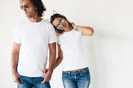 Zwei Hipster Modelle Mann und Frau tragen blanc T-Shirt, Jeans und Sonnenbrille posiert gegen weiße Wand, getönten Foto, Front-T-Shirt Mockup für Paare Standard-Bild