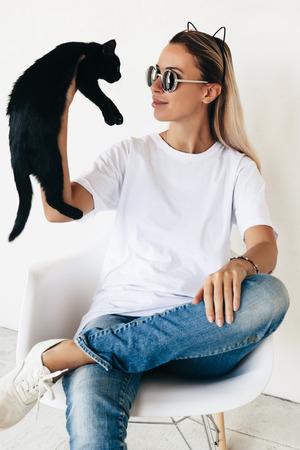 블랑 t- 셔츠, 청바지, 스 니 커 즈의 자에 앉아서 검은 고양이, 톤된 사진, 앞 tshirt 모델, hipster 스타일