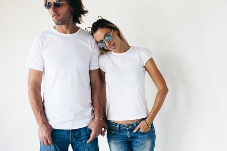 Dos modelos de última moda hombre y mujer con blanc camiseta, pantalones vaqueros y gafas de sol posando contra la pared blanca, foto entonada, maqueta camiseta frontal para pareja