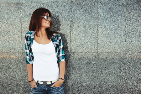Hipster girl wearing white t-shirt and fashion sunglasses posing against wall, swag street style Stock Photo