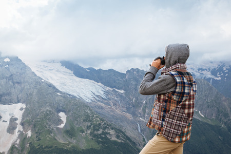 cold season: Man drinking hot coffee in thermos mug and looking into the mountains in snow, winter hike, cold season