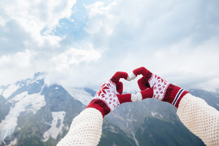 corazon en la mano: Closeup photo of hands in gloves showing love to the mountains, winter travelling