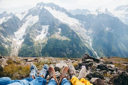 Caminantes descansando en la montaña, los pies sobre la vista alpina
