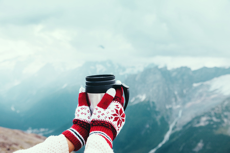cold season: Closeup photo of thermos mug with tea in travelers hand over out of focus mountains view with snow, tourizm in cold season