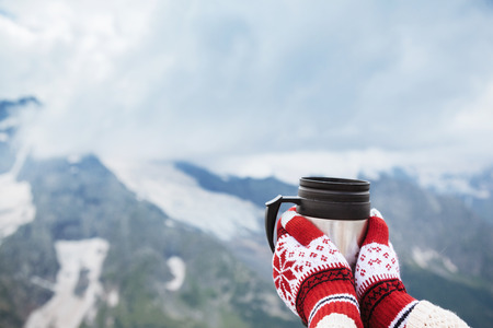Closeup photo of thermos mug with tea in travelers hand over out of focus mountains view with snow, tourizm in cold season