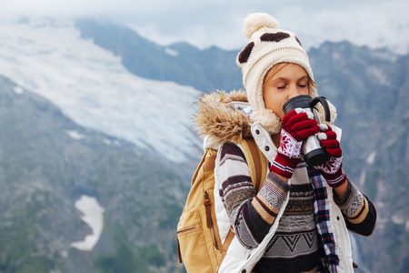 Traveler drinking tea in thermos mug in mountains with snow, winter hiking Stock Photo