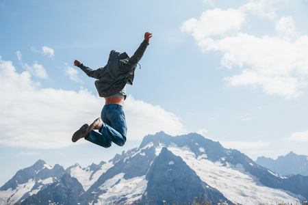 Onherkenbare man springen op de top van de berg over blauwe luchten, vrijheid en vreugde